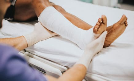 person on hospital bed with nurse bandaging right leg and ankle