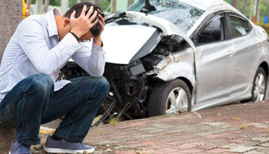 Man worried sitting outside wrecked car