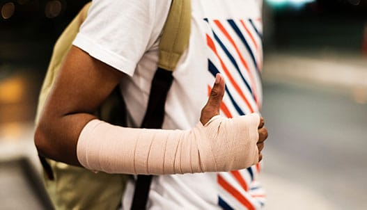 close up of man with right forearm, wrist, and hand in bandage giving thumbs up