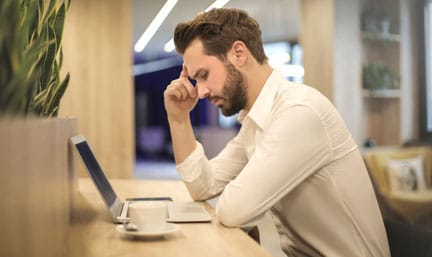 worried man sitting in front of laptop