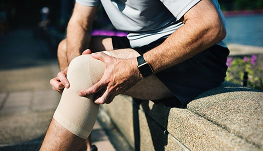 Man with knee brace holding his knee