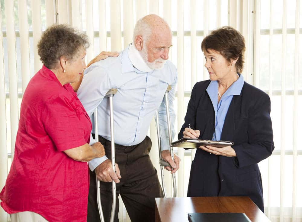 Injured man on crutches having a discussion with a professionally dressed woman that is taking notes