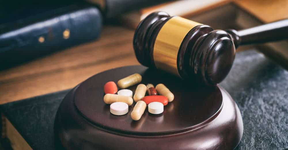 various prescription pills sitting on judge's gavel