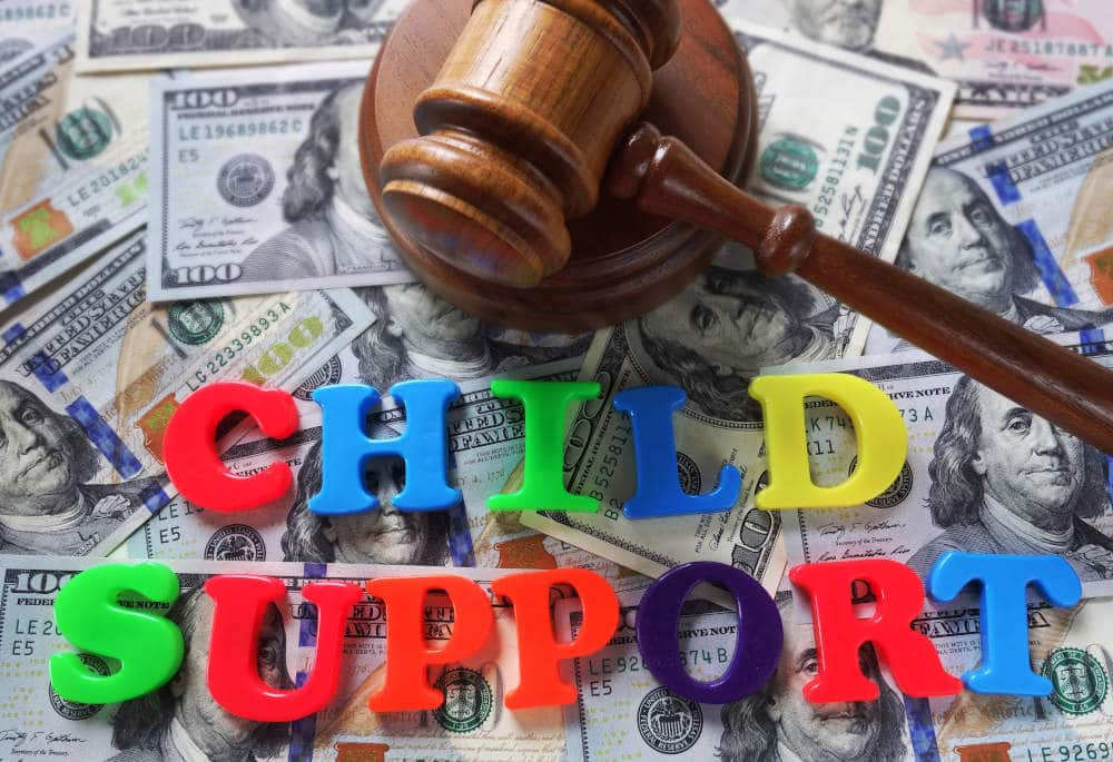 the words child support spelled out in colorful plastic letters sitting on background of $100 bills with gavel
