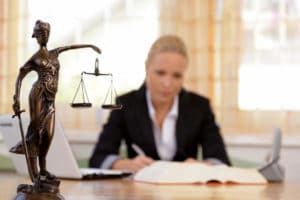 Professionally dressed woman working in office with statue of lady justice in foreground
