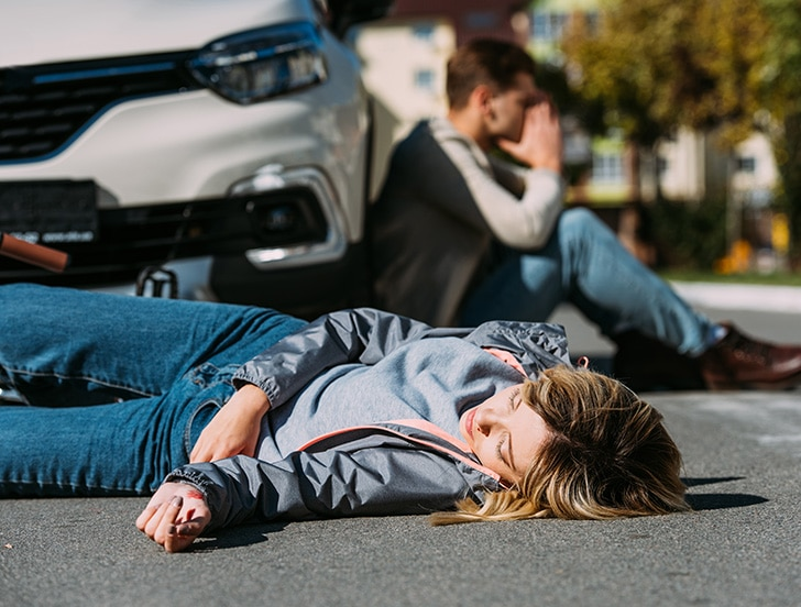 Woman laying in street in front of car that hit her