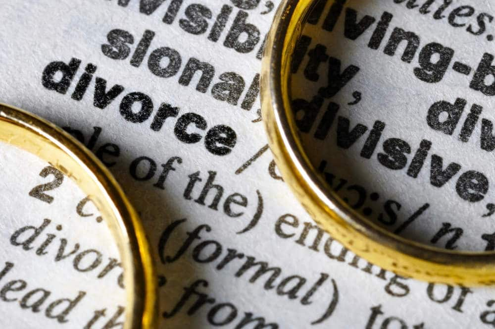 close up of the word divorce in a dictionary with gold wedding bands